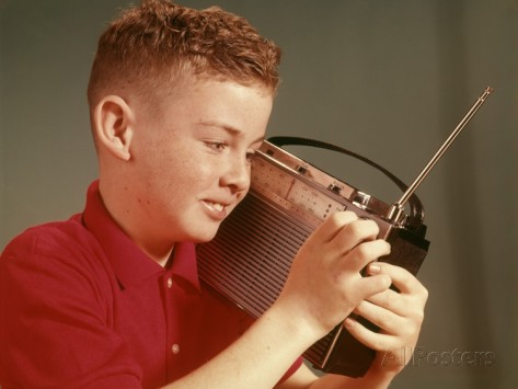 1960s-young-red-hair-pre-teen-boy-listening-to-portable-transistor-radio-held-up-to-ear